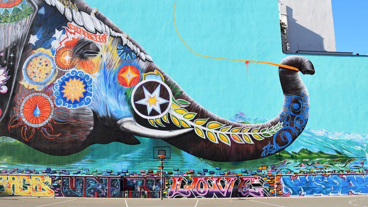 Buntes Streetartgemälde eines Elefanten mit Weltballon in Berlin-Kreuzberg